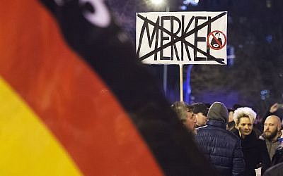 In this file photo from February 24, 2016, people wave German flags in Erfurt, central Germany, during a demonstration initiated by the Alternative for Germany (AfD) party. (AP Photo/Jens Meyer, file)