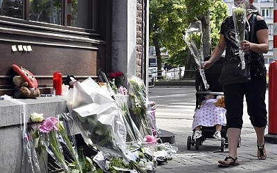 A woman leaves flowers at the scene of a shooting in Liege, Belgium, May 30, 2018. (AP Photo/Geert Vanden Wijngaert)