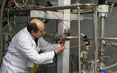 Illustrative: An unidentified International Atomic Energy Agency inspector cuts the connections between the twin cascades for 20 percent uranium enrichment at the Natanz facility, some 200 miles (322 kilometers) south of the capital Tehran, Iran, Monday, January 20, 2014. (AP/IRNA, Kazem Ghane)