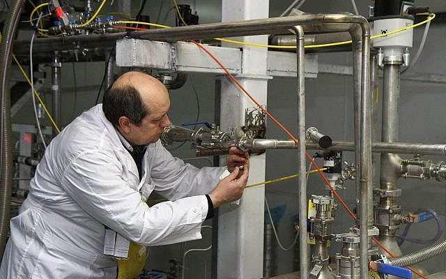 An unidentified International Atomic Energy Agency inspector cuts the connections between the twin cascades for 20 percent uranium enrichment at the Natanz facility, some 200 miles (322 kilometers) south of the capital Tehran, Iran, Monday, January 20, 2014. (AP/IRNA, Kazem Ghane)