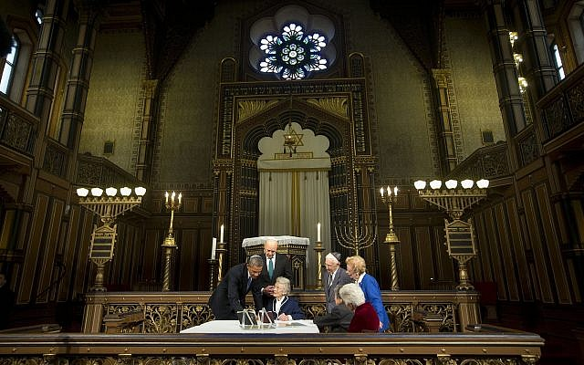 President Barack Obama and Swedish Prime Minister Fredrik Reinfeldt, center standing, listen to Nina Lagergren, 92, center, seated, as they look over artifacts and personal possession of Raoul Wallenberg at the Great Synagogue and Holocaust Memorial of Stockholm, Wednesday, September 4, 2013 in Stockholm. (AP/Pablo Martinez Monsivais)