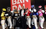 Haim Saban, center, creator of Power Rangers and Chairman and CEO of Saban Capital Group, poses with the Rangers outside the Bandai booth at the American International Toy Fair, Sunday, February 10, 2013, in New York. (Diane Bondareff/Invision for Saban Brands/AP)