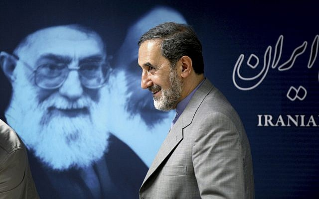 Iranian presidential candidate Ali Akbar Velayati, a former foreign minister, walks past a portrait of supreme leader Ayatollah Ali Khamenei at the conclusion of his press conference in Tehran, Iran, Monday, June 3, 2013. (AP Photo/Ebrahim Noroozi)