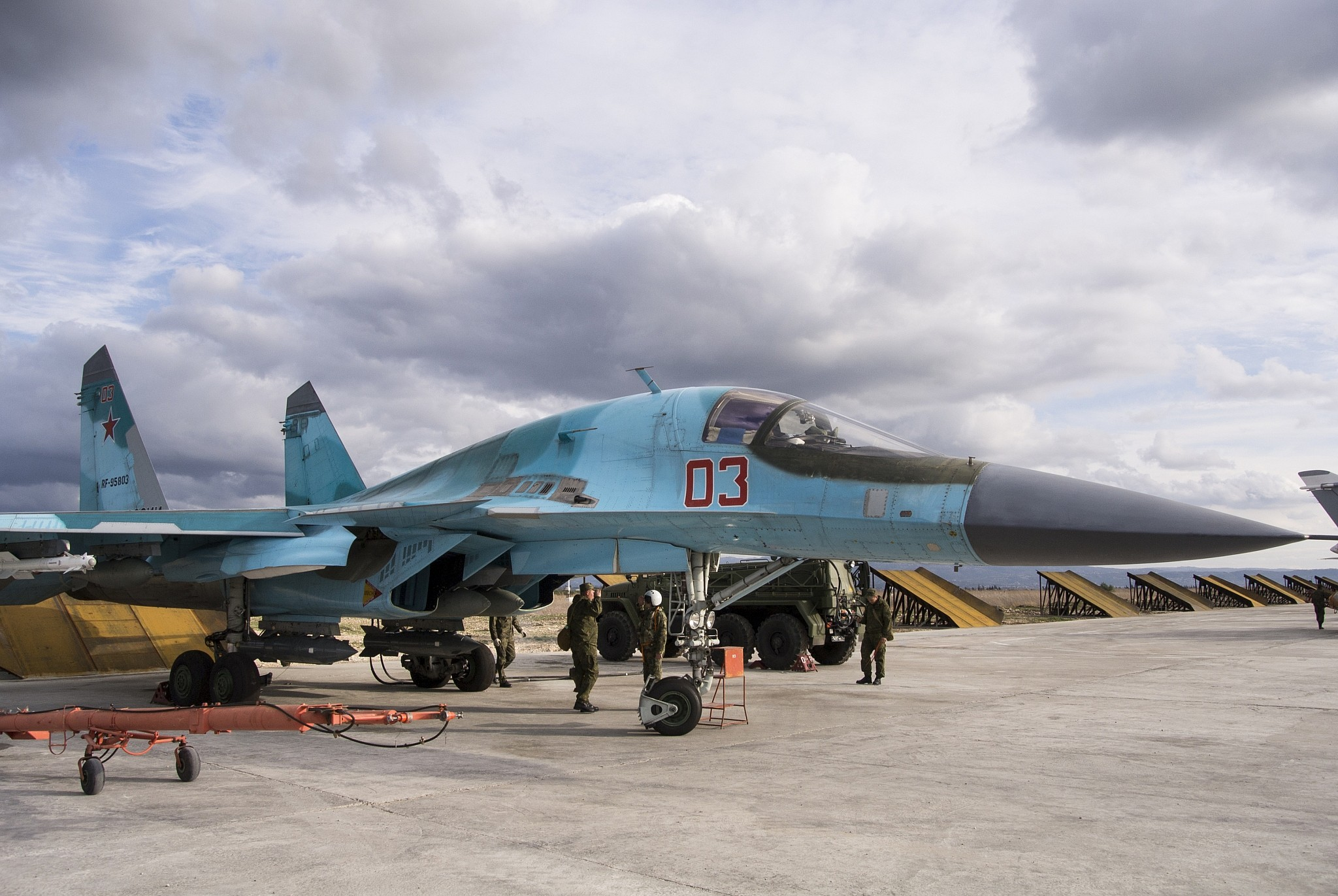 A Russian air force technician reports to a pilot that a Su-34 bomber is ready for a combat mission at Hemeimeem airbase in Syria