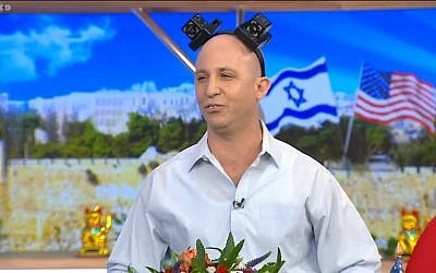 Still from video of a comedy sketch by the Eretz Nehederet satire show depicting Education Minister Naftali Bennet wearing joke tefillin, May 16, 2018. (Screen capture: Hadashot news)