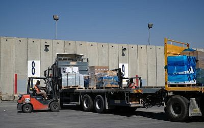 Workers load medical supplies onto a truck bound for the Gaza Strip at the Kerem Shalom Crossing on May 13, 2018. (Judah Ari Gross/Times of Israel)