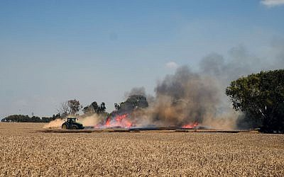 An Israeli farmer puts out a fire in his wheat field that was started by an incendiary kite from Gaza, outside Kibbutz Nahal Oz in southern Israel, on May 14, 2018. (Judah Ari Gross/Times of Israel)