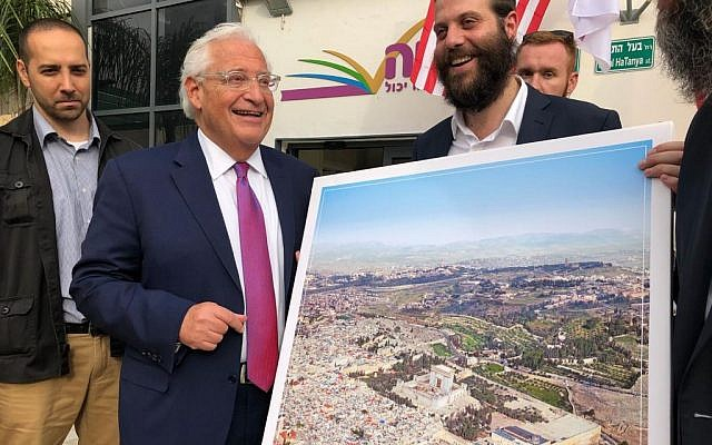 "US Ambassador to Israel David Friedman receives a poster of the Jewish Temple replacing the Muslim Dome on the Rock on Jerusalem's Temple Mount, at an event for the Achiya educational nonprofit in Bney Brak, May 22, 2018. Achiya has apologized to the US Embassy for the incident after the embassy clarified US policy backs the ""status quo"" at the holy site. (Twitter screen capture)"