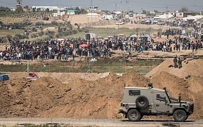 IDF soldiers on the Israeli side of the border with the Gaza Strip as thousands of Palestinians demonstrate near the border fence, April 6, 2018. (Hadas Parush/Flash90)