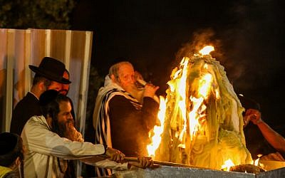 Rabbi Eliezer Berland lights a bonfire during the celebrations of the Jewish holiday of Lag Baomer on Mt. Meron in northern Israel on May 3, 2018. (Shlomi Cohen/Flash90)