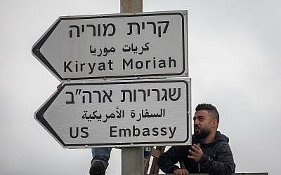 Jerusalem municipality workers hang a road sign directing to the US Embassy near the US Consulate in Jerusalem, on May 7, 2018. (Yonatan Sindel/Flash90)