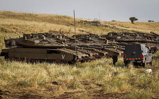 Israeli soldiers seen beside tanks near the Israeli-Syrian border in the Golan Heights on May 10, 2018 (Basel Awidat/Flash90)