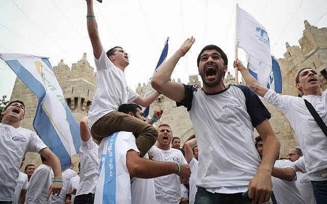 Thousands of Israelis  wave the Israeli flags as they celebrate Jerusalem Day by dancing through Damascus Gate on their way to the Western Wall.  on May 13, 2018. (Yonatan Sindel/Flash90