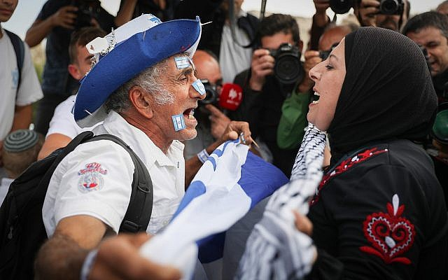 A Jewish man waving the Israeli flag argues with an Arab woman as thousands celebrate Jerusalem Day by dancing through Damascus Gate on their way to the Western Wall in the Old City of Jerusalem, May 13, 2018. (Yonatan Sindel/Flash90)