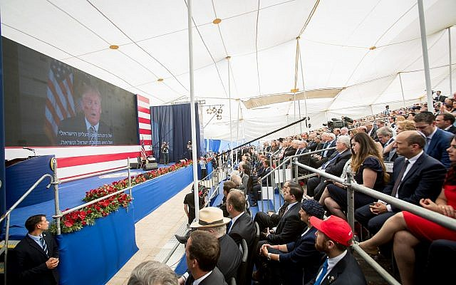 People watch as US President Donald Trump speaks on a video screen during the official opening ceremony of the US embassy in Jerusalem on May 14, 2018. (Yonatan Sindel/Flash90)