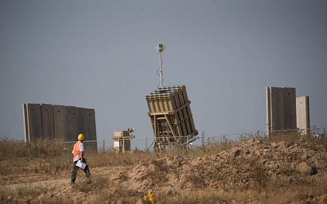 A worker walks by an Iron Dome missile defense battery near the city of Sderot in southern Israel on May 29, 2018. (Yonatan Sindel/Flash90)