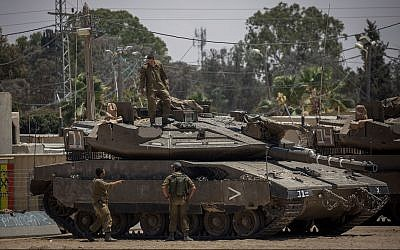 IDF soldiers seen near tanks at an army base near the border with the Gaza Strip, May 30, 2018. (Yonatan Sindel/Flash90)