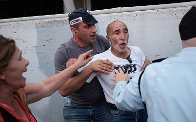 Police officers detain an activist during a protest of disabled people and activists, calling for better health care and allowances in Tel Aviv on May 31, 2018. (Tomer Neuberg/Flash90)