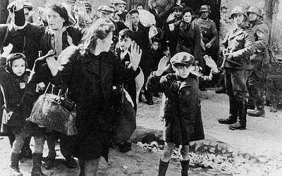 A Jewish boy surrenders in Warsaw -- the most well-known photograph taken during the 1943 Warsaw Ghetto uprising, in which a boy holds his hands over his head while SS-Rottenführer Josef Blösche points a submachine gun in his direction. (Wikipedia, public domain)