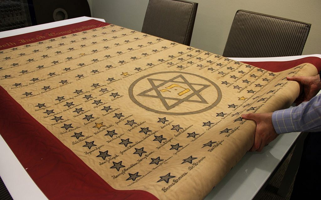 Dr. Josh Furman unfolding a copy of a 1940's banner from the Beth Jacob Synagogue honoring Jewish veterans from the Houston area who served in World War II. (Tracy Frydberg/Hurricane Harvey)