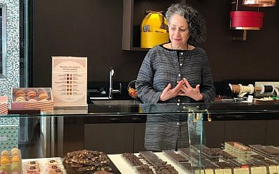 Rabbi Deborah Prinz points on front of a display of different chocolates at La Maison du Chocolat, perhaps the holiest site for cocoa lovers on the Upper East Side (Danielle Ziri/ Times of Israel)
