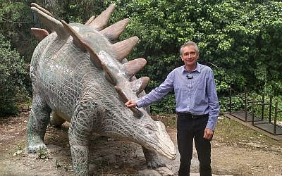 Dr. Evgeny Reznitsky, educational director of the Natural History Museum in Jerusalem, standing next to a dinosaur statue in the museum's outer garden on May 1, 2018. (Michael Bachner/Times of Israel)