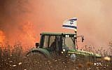 An undated photo of an Israeli farmer in the Gaza-area driving his tractor next to a  field apparently set aflame by a burning kite flown from the Gaza Strip. (Courtesy)
