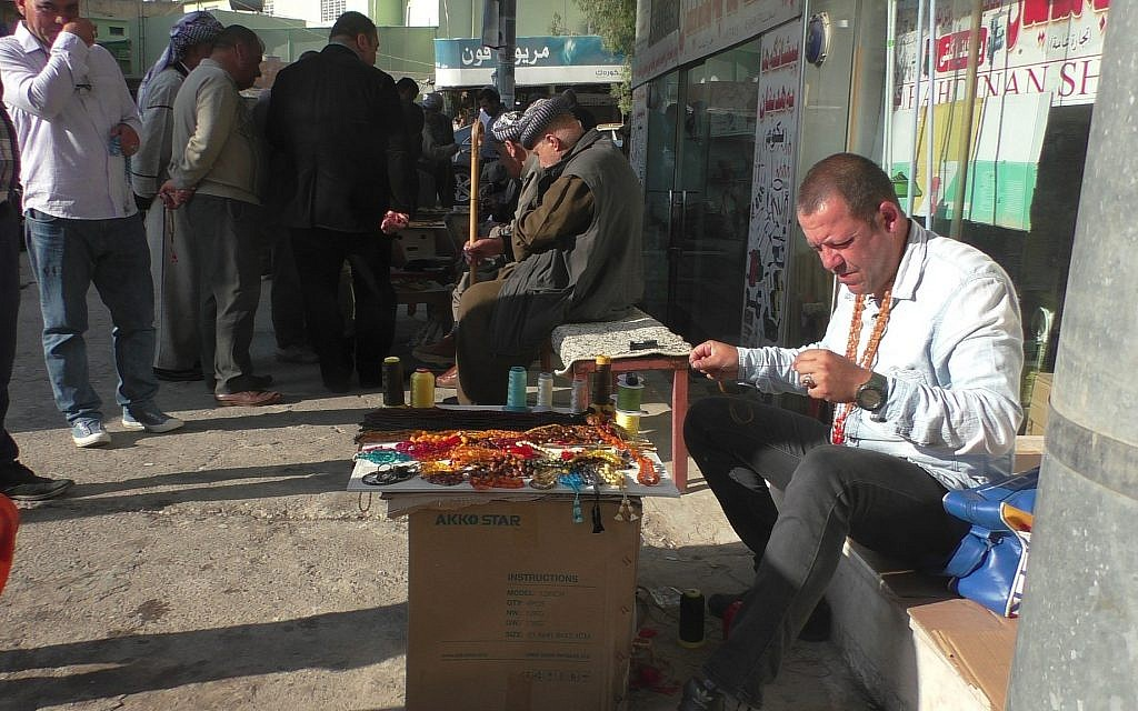A man sells prayer beads on the street in Dohuk, Iraqi Kurdistan, on election day, May 12, 2018. (Ziv Genesove/ Times of Israel)