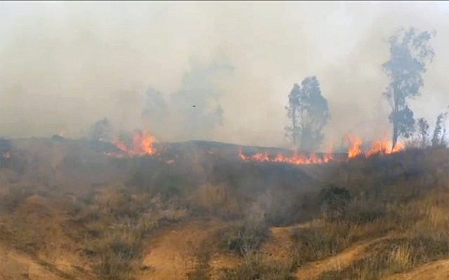Smoke and flames rise from grassland Kibbutz Be'eri in southern Israel after Palestinians flew a kite laden with a Molotov cocktail over the border on May 2, 2018. (Screen capture/Rafi Bavian)