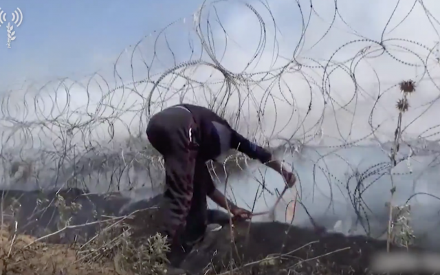 Illustrative. A Gazan takes bolt cutters to a border fence in footage released by the IDF from May 14 violence at the border (Israel Defense Forces)