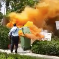 Orange smoke rises from smoke bombs near Prime Minister Benjamin Netanyahu's  home in Caesarea, May 25, 2018 (Kan TV news screenshot)