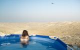 A Tekoa resident sits in a pool overlooking the Judean desert. (Neta Mor/Unsettling)