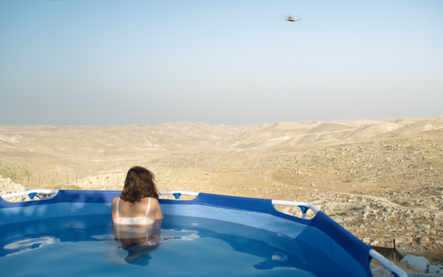 A Tekoa resident sits in a pool overlooking the Judean desert. (Neta Mor/Unsettled)