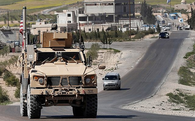 A US soldier sits on an armored vehicle on a road leading to the tense front line in Manbij, north Syria, Wednesday, April 4, 2018. (AP/Hussein Malla)