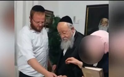 Baruch Klein (l) with his grandfather MK Menachem Eliezer Moses of UTJ. (Screen capture: Kann news)