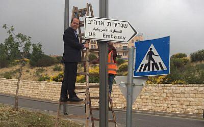 Jerusalem Mayor Nir Barkat hangs the first sign pointing to the new US Embassy in Jerusalem, May 7, 2018 (Jerusalem Municipality)