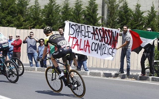 Anti-Israel protesters hold a banner reading 'Israel assassinates, Italy complicit' before the start of the 4th stage of the Giro d'Italia cycling race between Catania and Caltagirone in Sicily, May 8, 2017. (AFP PHOTO / Luk Benies)