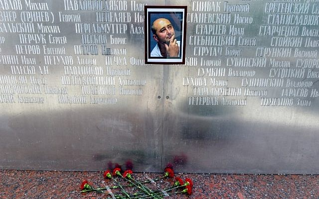 Flowers are placed under a picture of 41-year-old anti-Kremlin reporter Arkady Babchenko on the memorial wall of Moscow's journalists house on May 30, 2018, until his death was revealed to have been faked. (AFP PHOTO / Vasily MAXIMOV)