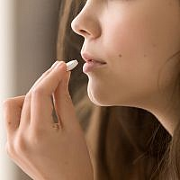 Illustrative: Close up of woman taking a pill (iStock)