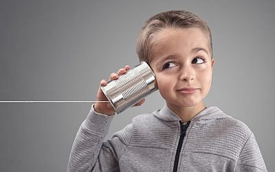 Illustrative: Boy listening via tin can phone. (iStock)