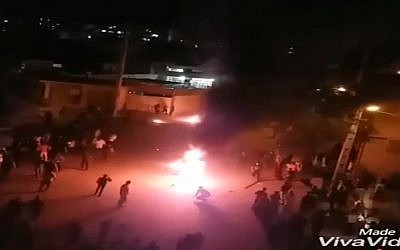 Protestors set fire to a structure in Kazeroon, Iran, May 17, 2018. (Screen capture)