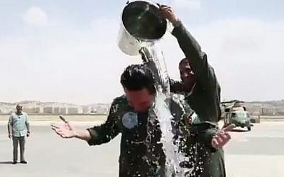 Jordanian Crown Prince Hussein ibn Abdullah gets the traditional celebratory treatment of a bucket of water over the head after his first solo helicopter flight. (Twitter)