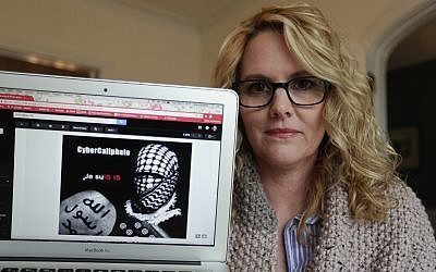 Angela Ricketts poses on April 9, 2018, with a screen shot of a message she received from a group claiming to be Islamic State supporters, in Bloomington, Ind. (AP Photo/Michael Conroy)
