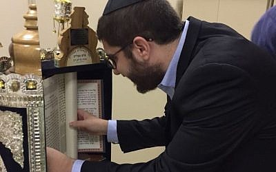 Rabbi Mendy Aboutboul of the Edmond J. Safra Ipanema synagogue in Rio de Janeiro inspects the sefer haftarah scoll found by police in a local shantytown, on May 28, 2018. (Courtesy of Edmond J. Safra Ipanema synagogue via JTA)