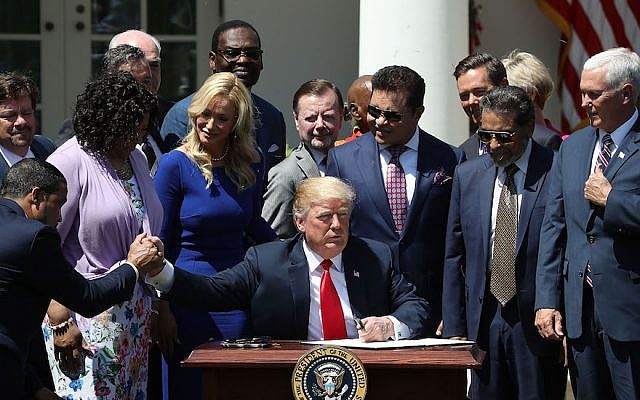 President Donald Trump, flanked by members of faith-based communities, signs a proclamation declaring a National Day of Prayer during an event in the Rose Garden at the White House, May 3, 2018. (Mark Wilson/Getty Images, via JTA)