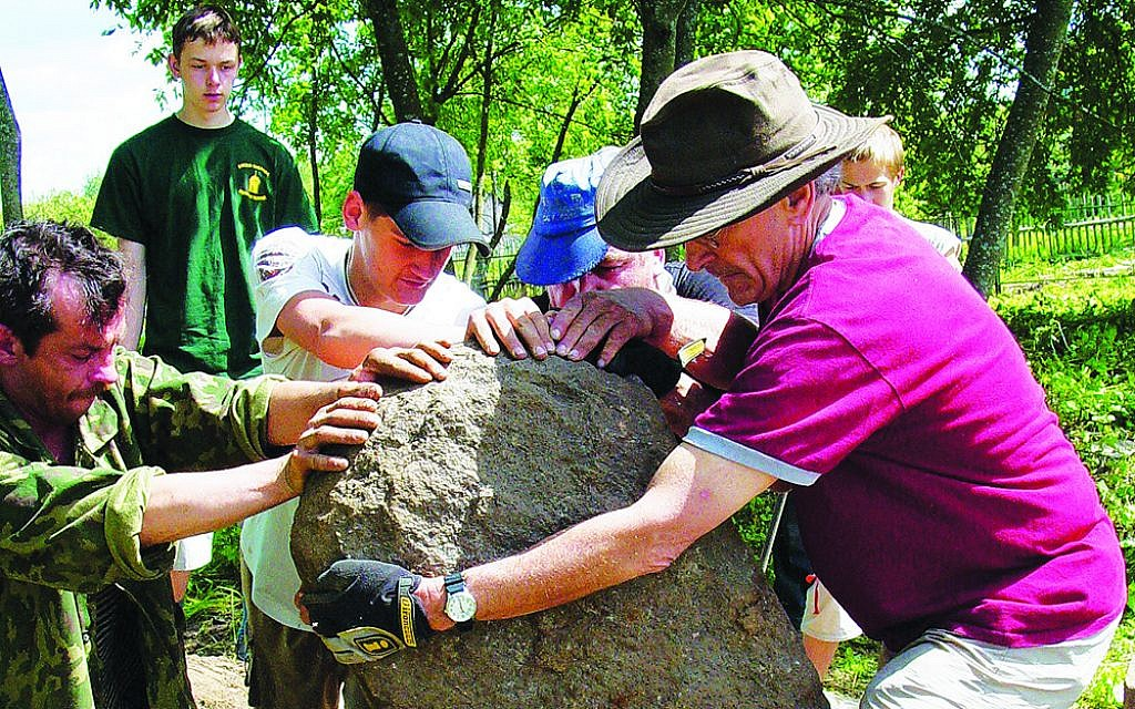 Dr. Michael Lozman, foreground, fixing up a Jewish cemetery in Belarus. (Courtesy)