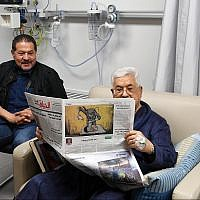 Palestinian Authority President Mahmoud Abbas shown recovering in hospital and  reading a newspaper, on the back page of which is a cartoon portraying an Israeli soldier poisoning a Palestinian baby, May 22, 2018. (Wafa news agency)