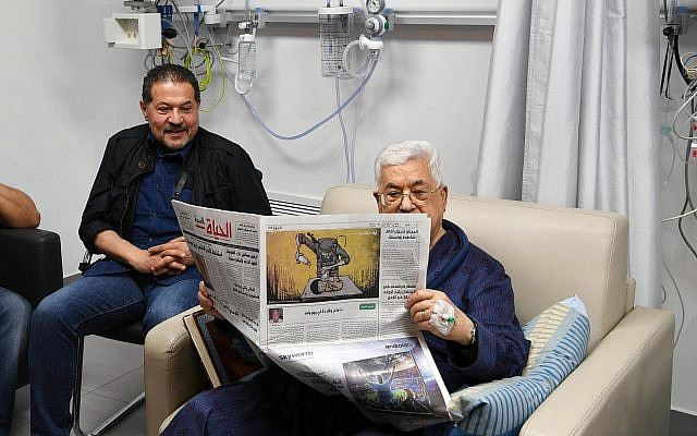 Palestinian Authority President Mahmoud Abbas shown recovering in a hospital on May 22, 2018, reading a newspaper (Wafa news agency)