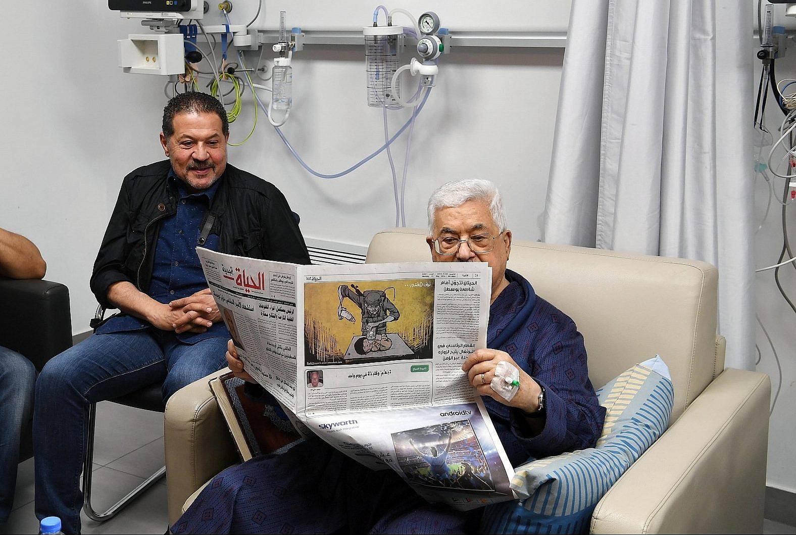 Palestinian Authority President Mahmoud Abbas shown recovering in hospital and reading a newspaper on the back page of which is a cartoon portraying an Israeli soldier poisoning a Palestinian baby