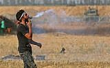 A Palestinian protester holds a tear gas canister in his mouth during a demonstration along the border with Israel east of Khan Yunis in the southern Gaza strip on June 1, 2018. (AFP PHOTO / SAID KHATIB)